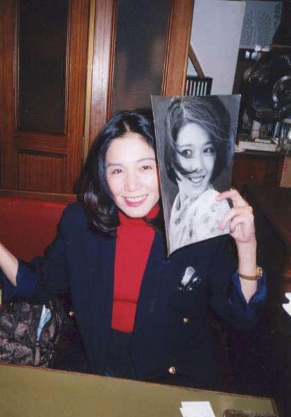 若いころの写真を持って笑っているひし美ゆり子の画像